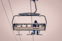 A lonely snowboarder sitting completely alone in a chairlift. Freezing cold foggy weather is making this ride extremely uncomfortable. Taken in Tignes in the French Alps on a winter day.