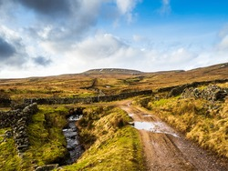 A lonely track leads through beautiful open moorland and past a stream and a dry stone wall, towards the imposing Dead Mans Hill in the distance. Nidderdale. Yorkshire Dales National Park