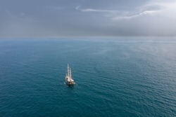 A lonely vessel is sailing on a flat sea towards an incoming storm