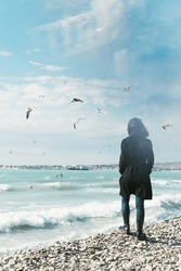 A lonely woman stands on the shore of a stormy sea. Seagulls fly around her. The concept of expectation of changes in life.