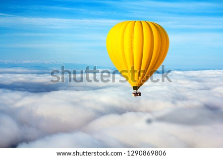 A lonely yellow hot air balloon floats above the clouds. Concept leader, success, loneliness, victory #1290869806