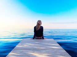 A lonely young blonde woman sitting wooden pier. Girl sitting on a wooden pier and looking at the ocean. Woman sitting on wooden dock looking at lake