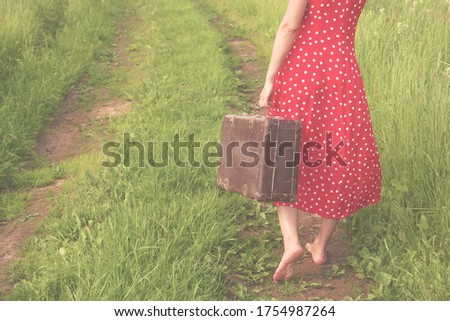 a lonely young woman in a red polka-dot dress with an old suitcase walks barefoot along a country road. Back View                              Stock photo ©