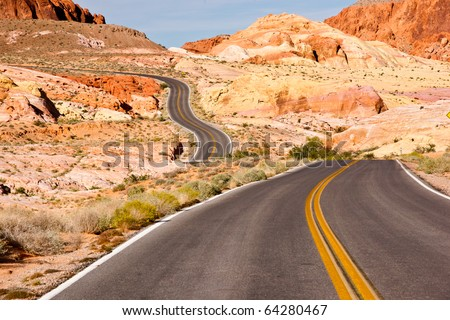 A long and winding road through colorful desert sandstone