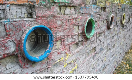 A long brick wall with oval through holes. Old plaster and paint are sprinkled #1537795490