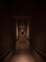 A long dark stair walkway leading underground with dark lighting giving an ominous feel.