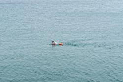 A long-distance swimmer with orange cap and dry bag swimming in endless open ocean water