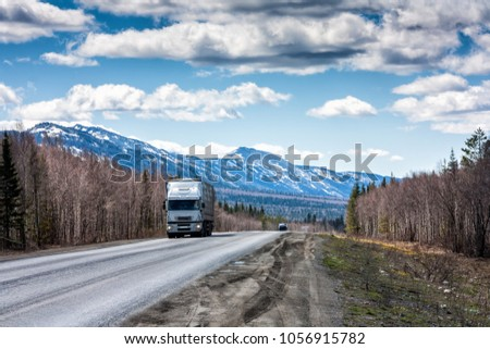 A long-distance truck with a semitrailer moves on the road among the mountains covered with snow #1056915782