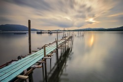 A long exposure image of empty old wooden jetty during sunset