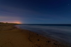 A long exposure night photograph of Easthaven beach with the tide out, and the lights of Arbroath seen above the horizon on a December Night.