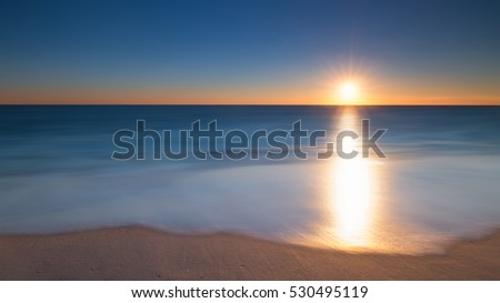 A long exposure of a sunrise and wave washing up the beach.  #530495119