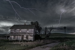 A long exposure of an old, dilapidated haunted house in rural Midwest at night, framed by eerie dark skies and lightning.