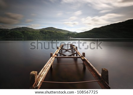 A long exposure of an old jetty on the shore of Loch Lomond looking over to Inversnaid and Lomond mountains.
