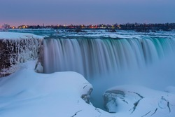 A long exposure of Niagara Falls during a wintery evening, covered in snow and ice.