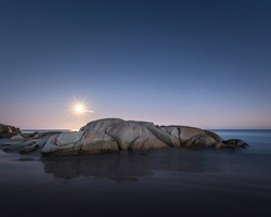A long exposure of the Bloodmoon rising over rocks on a beach during the lunar eclipse at blue hour.  The moon cast an incredible shadow of the rock creating a reflection underneath the stars