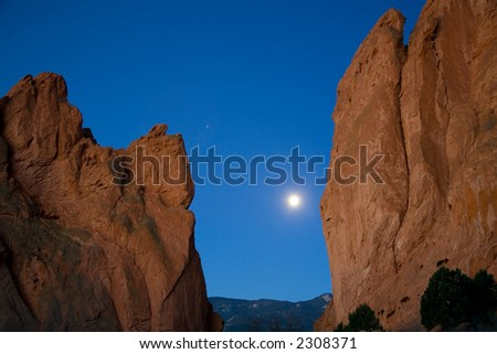 A long exposure of the Moon and Jupiter between two of the large rock formations of the Garden of the Gods Park in Colorado Springs.