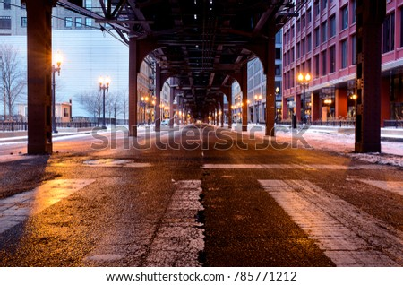 A long exposure photo. Under the train tracks in downtown Chicago. The street is empty on this winter morning, and the street has a bright shine from melted snow.
