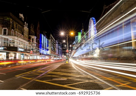 A long exposure photograph of a busy junction of Edinburgh at night during the Christmas Market season with the Ferris Wheel in the background. #692925736