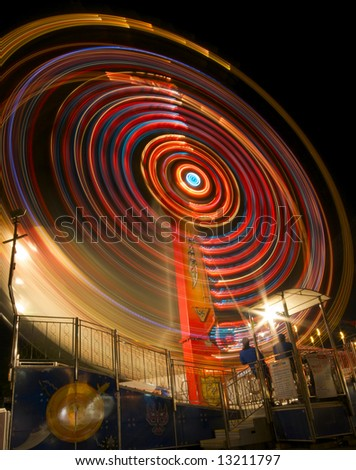 A long exposure photograph of a carnival ride shows a swirl of colorful lights