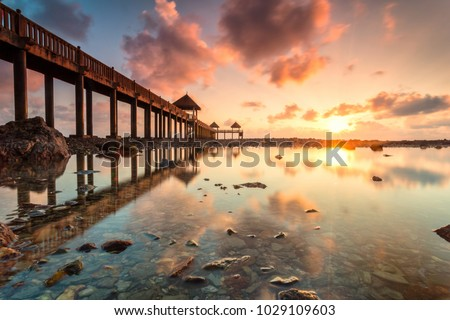 A Long exposure picture of golden sunrise with stone jetty with reflection
