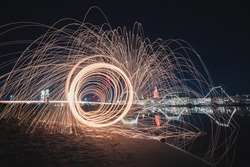 A long exposure shot of spinning steel wool creating sparks of light in a dark night sky