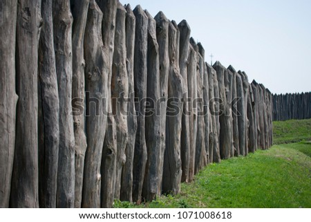 a long fence of logs protects...
