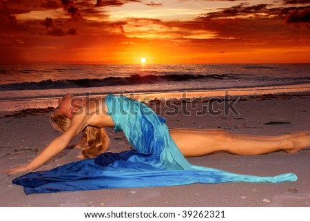 A long haired blonde woman is stretched out on the beach at sunset in profile with her legs straight out and her back arched as she looks up at the sky.