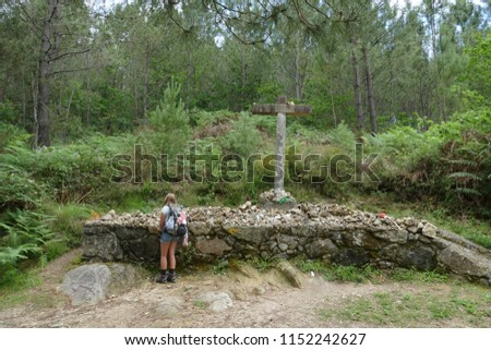 A long-haired girl (fourteen-year-old) marveling at a Christian cross, where many pilgrims have left stones and other souvenirs on the Pilgrim-Way of St. James - near Rubiaes in Northern Portugal #1152242627