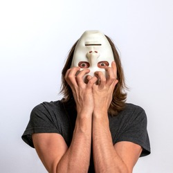 A long-haired man in a gray T-shirt covers his face with a white mask upside down and tries to tear it off himself. The concept of personality crisis, fear, paranoia or mental disorders.