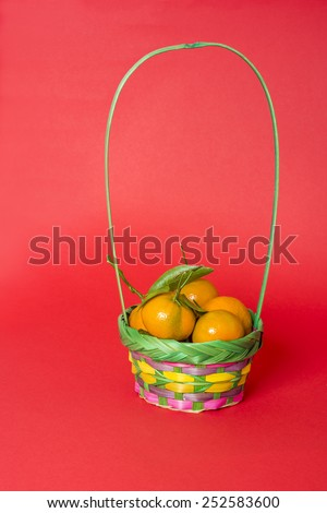 stock-photo-a-long-handle-basket-of-mandarin-oranges-with-green-leaf-isolated-on-red-background-traditional-252583600.jpg