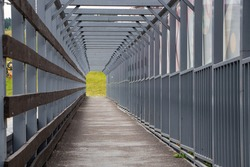 A long pedestrian tunnel with metal arches and mesh design. Aerial pedestrian crossing over the highway, perspective goes to the horizon, a empty tunnel no people.