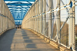 A long pedestrian tunnel with metal mesh design. Aerial pedestrian crossing over the highway, perspective goes to the horizon.