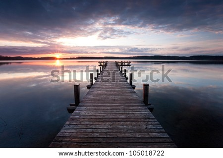 a long pier leading out onto the lake, sunrise on lake, long way out
