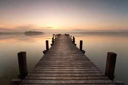a long pier leading out onto the lake, sunrise on lake, long way out with fog
