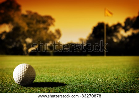 A long putt on the 18th green as sunset closes in - stock photo