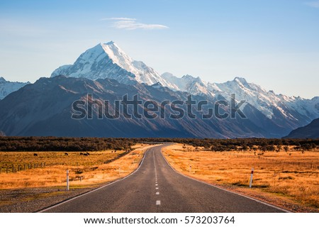 A long road leading to a large snow capped mountain on a sunny day #573203764