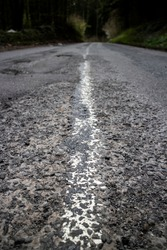 A long road, showing the gritty detail of its texture and painted white line in the middle. There is a forest up ahead, at the end of the road. Image is a concept for the long, lonely road to success.
