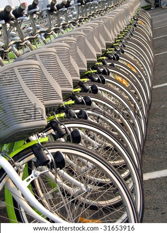 A long row of green rental bicycles with baskets