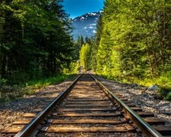 A long section of train track runs through a British Columbia forest with a snow covered mountain in the background.