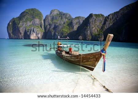 stock photo : A long tail boat sits in Maya Bay, Koh Phi Phi Ley, Thailand.