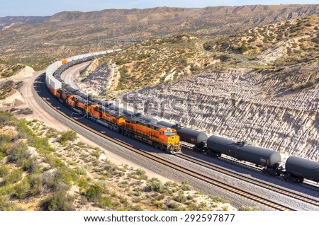 A long train loaded with double-stack white cargo containers winds its way around tight s-curves in mountain countryside. All ID marks removed. A line of tanker cars waiting. California, near I-15.
