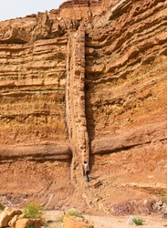 a long vertical magmatic igneous dike cuts through red and orange horizontal layers of sedimentary rock in nahal Ardon in Makhtesh Ramon in Israel