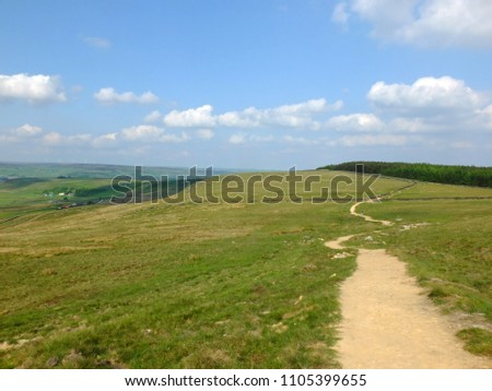 a long winding footpath running into the distance in stoodley moor in yorkshire with fields and farms in the distance with the pennine hills on the horizon on a sunny day with blue sky and clouds