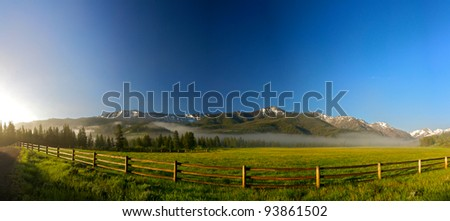 A long wooden rail fence stretches across the front of a Wyoming ranch.