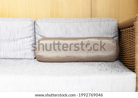 A long wooden wicker sofa and cotton cushions in the interior of the home living room