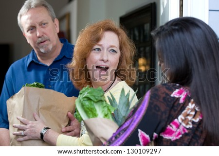 A look of surprise emotion is on the recipients faces as a charity relief worker brings bags of food and groceries to the hungry.
