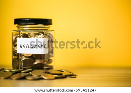 A lot coins in glass money jar with yellow background. Saving for Retirement concept.