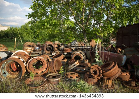 A lot of automobile or truck rims and other parts, awaiting to be used again or to recycling, in a car graveyard, Kozani, Greece. #1436454893