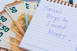 A lot of bills spread on table and assorted amounts and note smart ways to invest money