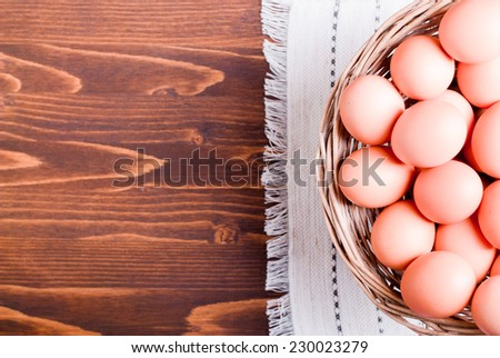 a lot of brown eggs in a wicker basket on a brown table top view on the left space for text